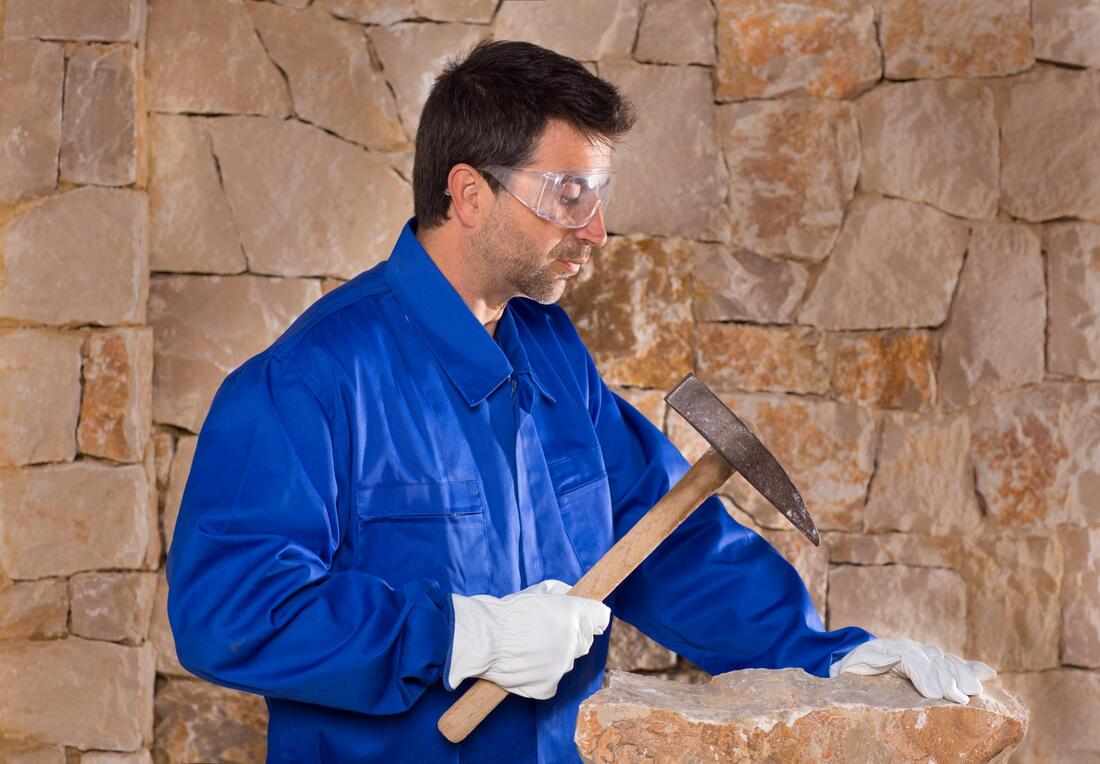 man breaking stone with hammer